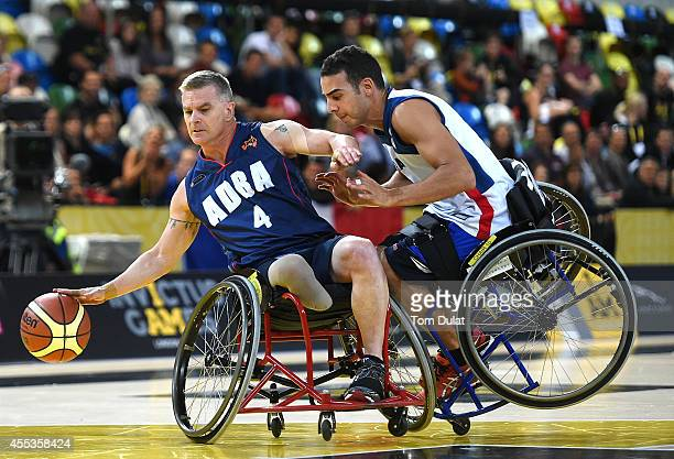 Tony Benfer of Australia and Lotfi Guatnaoi of France in action during the Wheelchair Basketball match between Australia and France on Day Three of...