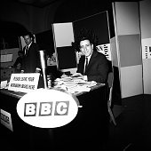 Tony Bennett signs a pile of autograph books while appearing on BBC radio show Pop Inn London 1965