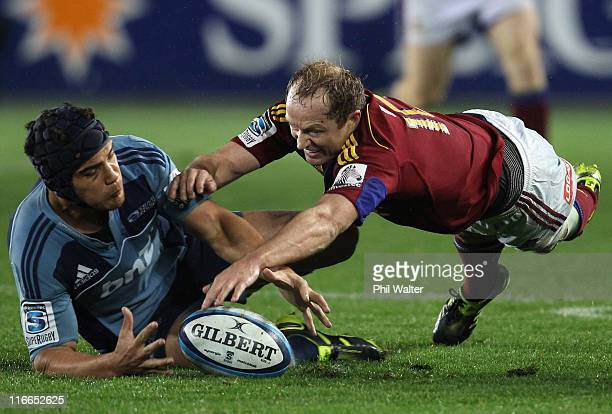 Tony Brown of the Highlanders and Benson Stanley of the Blues leap on the loose ball during the round 18 Super Rugby match between the Blues and the...