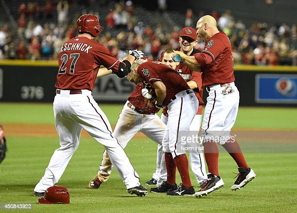 Tony Campana of the Arizona Diamondbacks drives in the winning run against the Milwaukee Brewers in the ninth inning and is congratulated by...