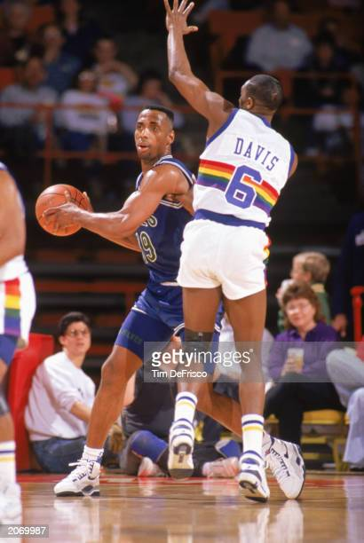 Tony Campbell of the Minnesota Timberwolves looks to pass while defended by Walter Davis of the Denver Nuggets in a game at McNichols Sports Arena in...