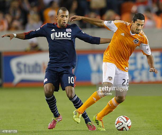 Tony Cascio of Houston Dynamo dribbles around Teal Bunbury of New England Revolution at BBVA Compass Stadium on March 8 2014 in Houston Texas