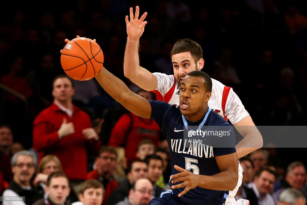 Tony Chennault #5 (foreground) of the Villanova Wildcats attempts to control the ball in the first half against Luke Hancock #11 of the Louisville Cardinals during the quaterfinals of the Big East Men's Basketball Tournament at Madison Square Garden on March 14, 2013 in New York City.