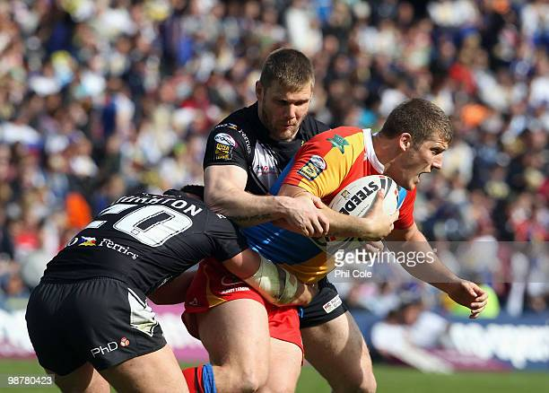 Tony Clubb of Harlequins gets tackled by Danny Houghton and Paul McShane during the Engage Rugby Super League Magic Weekend match between Hull FC and...