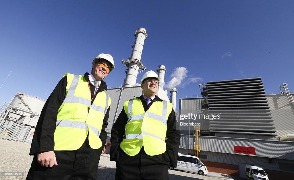 Tony Cocker, chief executive officer of EON U.K., part of EON AG, left, and Ed Davey, U.K. secretary of state for energy and climate change, pose for a photograph following the opening of a joint venture with the National Grid Plc at the company's plant on the Isle of Grain, U.K., on Thursday, Oct. 4, 2012. The National Grid Plc and E.ON have worked together to link two plants with twin pipelines, allowing surplus heat from electricity generation at E.ON's power station to heat LNG and convert it back to gas. Photographer: Chris Ratcliffe/Bloomberg via Getty Images