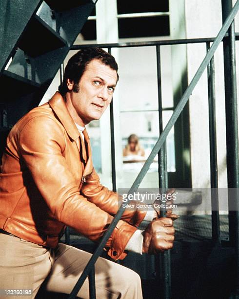 Tony Curtis US actor wearing a tan leather jacket and brown leather driving gloves walking up a flight of stairs in a publicity still issued for the...
