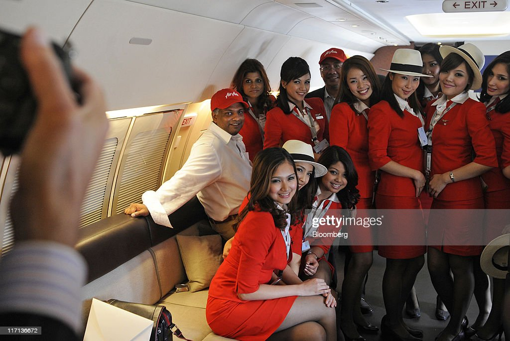 Tony Fernandes, chief executive officer of AirAsia Bhd., center, poses for photographs with AirAsia staff aboard an aircraft at the Paris Air Show in Paris, on Thursday, June 23, 2011. The 49th International Paris Air Show, the world's largest aviation and space industry show, takes place at Le Bourget airport June 20-26. Photographer: Fabrice Dimier/Bloomberg via Getty Images