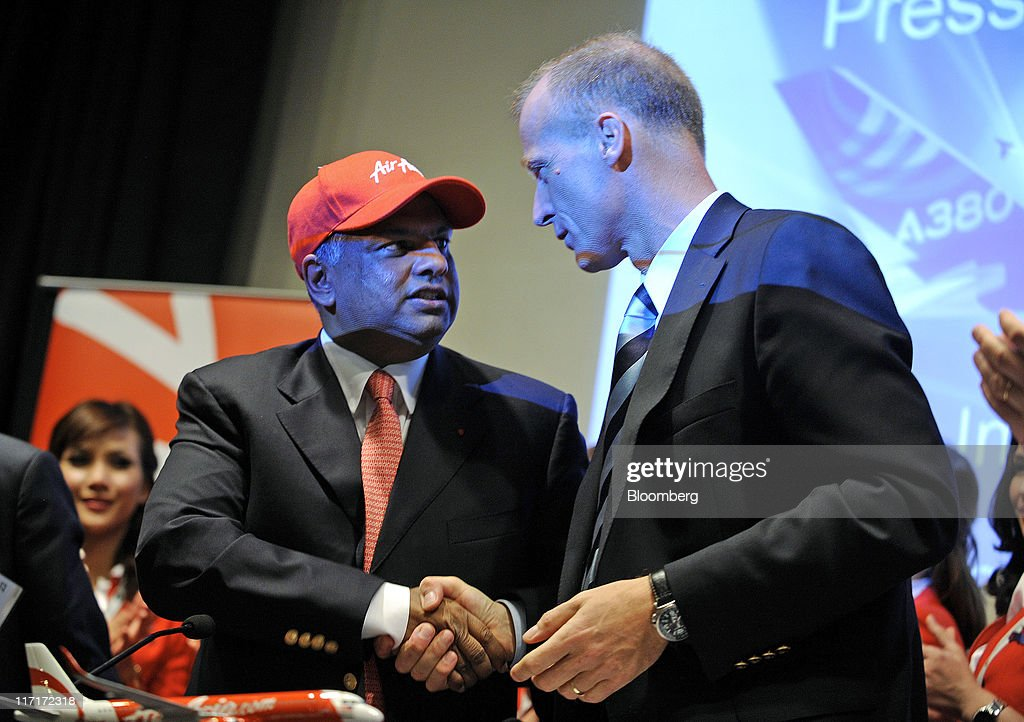 Tony Fernandes, chief executive officer of AirAsia Bhd, left, shakes hands with Tom Enders, chief executive officer of Airbus SAS, right, at a news conference to announce the purchase of 200 Airbus SAS A320neo aircraft at the Paris Air Show in Paris, France, on Wednesday, June 22, 2011. The 49th International Paris Air Show, the world's largest aviation and space industry show, takes place at Le Bourget airport June 20-26. Photographer: Fabrice Dimier/Bloomberg via Getty Images
