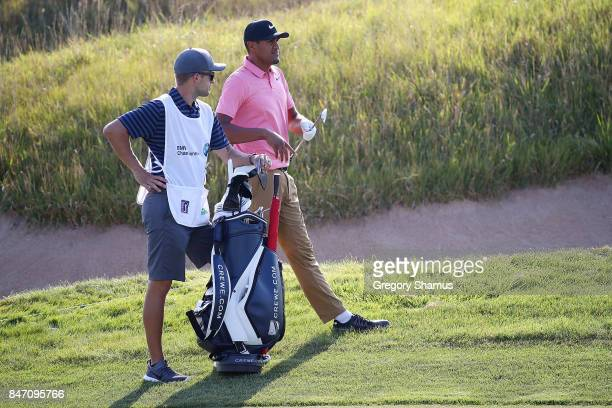 Tony Finau waits in the 18th fairway with his caddie during the first round of the BMW Championship at Conway Farms Golf Club on September 14 2017 in...