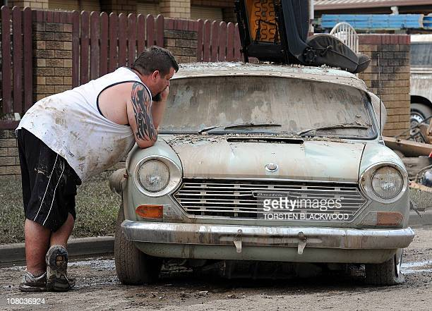 Tony Garcia surveys the remains of his father's flooddevastated '63 Austin Morris in Ipswich near Brisbane on January 14 2011 As the flood waters...
