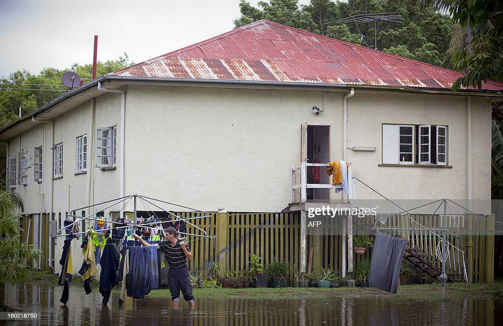 Tony Hall stands in floodwaters as he checks his washing on a clothes line in the inner Brisbane suburb of Newmarket on January 28, 2013. Helicopters plucked dozens of stranded Australians to safety in dramatic rooftop rescues on January 28 as severe floods swept the northeast, killing three people and inundating thousands of homes. AFP PHOTO / Patrick HAMILTON