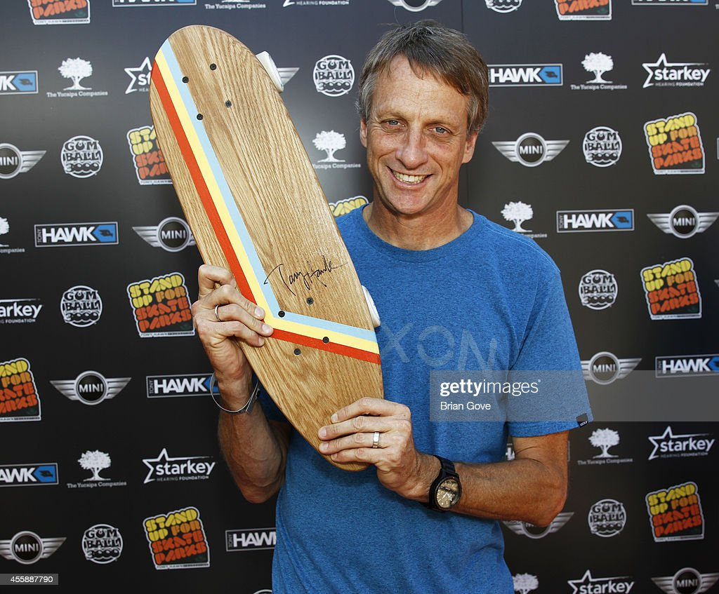 Tony Hawk holding up a signed Topico Skateboard at 11th Annual Tony Hawk's Stand Up For Skateparks Benefit at Ron Burkle's Green Acres Estate on...