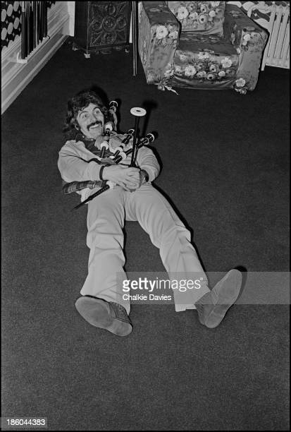 Tony Iommi Black Sabbath's guitarist wrestles with a set of bagpipes at his Manor House home in Staffordshire 1975