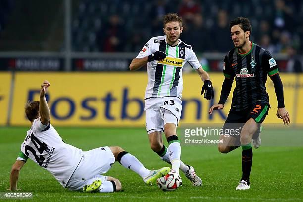 Tony Jantschke and Christoph Kramer of Moenchengladbach challenge Santiago Garcia of Bremen during the Bundesliga match between Borussia...