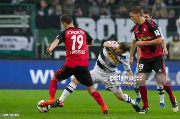 Tony Jantschke of Borussia Moenchengladbach Janik Haberer and Nils Petersen of SC Freiburg battle for the ball during the Bundesliga Match between...