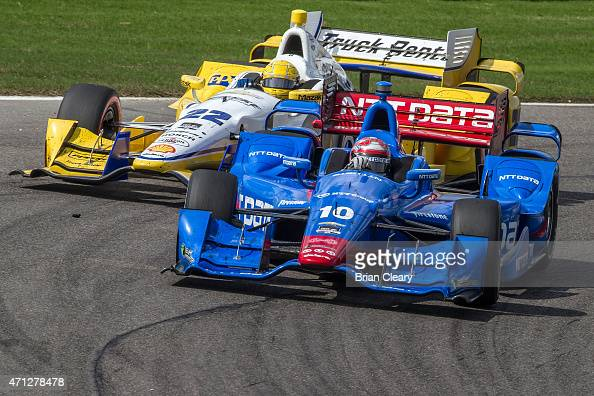 Tony Kanaan of Brazil in the Chevrolet Indy car and Simon Pagenaud of France in the Chevrolet Indy Car race together during the Indy Grand Prix of...