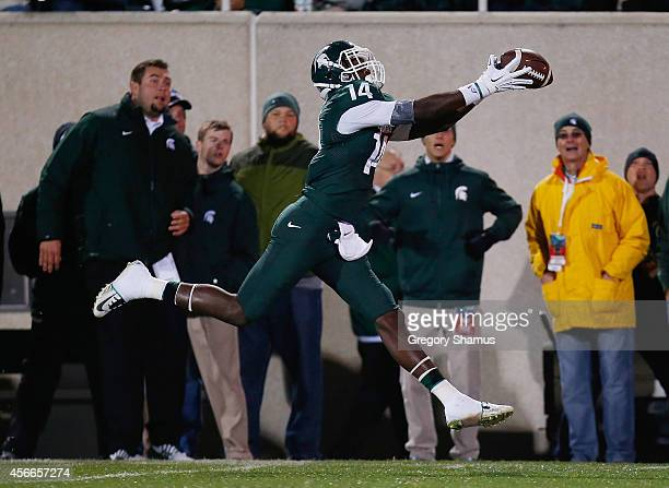 Tony Lippett of the Michigan State Spartans catches a firstquarter touchdown pass while playing the Nebraska Cornhuskers at Spartan Stadium on...