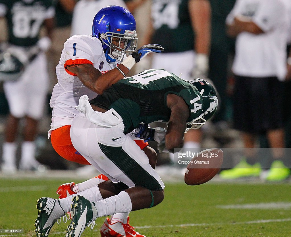 Tony Lippett #14 of the Michigan State Spartans fumbles while being hit by Bryan Douglas #1 of the Boise State Broncos at Spartan Stadium on August, 2010 in East Lansing, Michigan. Michigan State won the game 17-13.