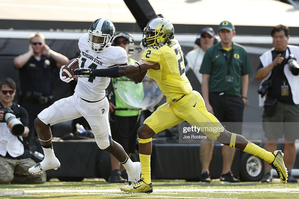 Tony Lippett of the Michigan State Spartans runs downfield after a 34yard reception against Tyree Robinson of the Oregon Ducks in the first half of...