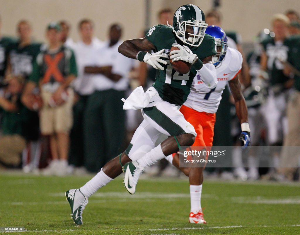 Tony Lippett #14 of the Michigan State Spartans runs for extra yards after a third quarter catch in front of Bryan Douglas #1 of the Boise State Broncos at Spartan Stadium on August, 2010 in East Lansing, Michigan. Michigan State won the game 17-13.