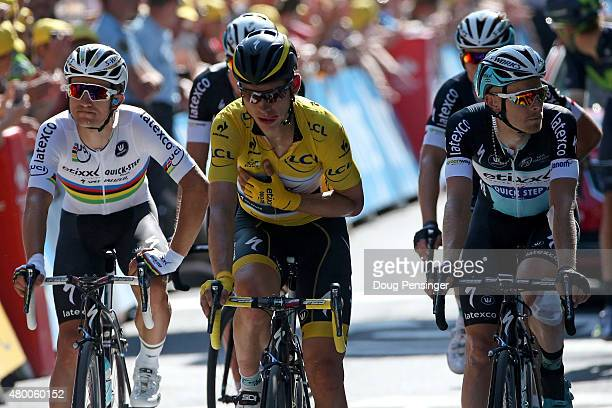 Tony Martin of Germany riding for EtixxQuickStep in the overall leader yellow jersey arrives at the finish with teammates Michal Kwiatkowski of...