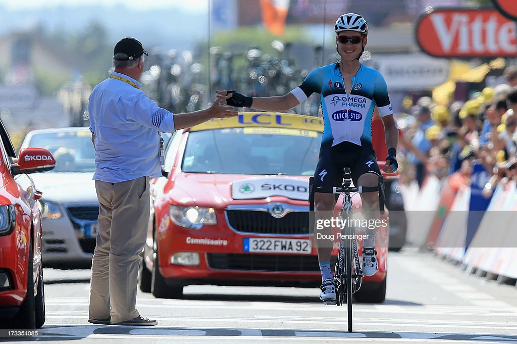 Tony Martin of Germany riding for Omega Pharma-Quick Step is greeted by Event Director Jean-Francois Pescheux as he crosses the finish line after his teammate Mark Cavendish won during stage thirteen of the 2013 Tour de France, a 173KM road stage from Tours to Saint-Amand-Montrond on July 12, 2013 in Saint-Amand-Montrond, France.