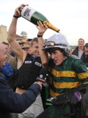 Tony McCoy riding Mountain Tunes is congratulated by fellow jockey Andrew Thornton after winning the Weatherbys Novices' Hurdle Race for his 4000th...