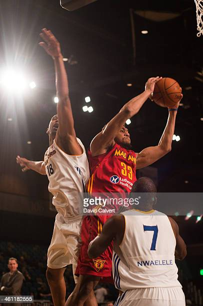 Tony Mitchell of the Fort Wayne Mad Ants pulls down a rebound away from Dominic McGuire and Daniel Nwaelele of the Santa Cruz Warriors during the...
