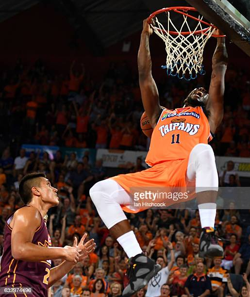 Tony Mitchell of the Taipans hangs from the rim after scoring during the round 17 NBL match between the Cairns Taipans and the Brisbane Bullets at...