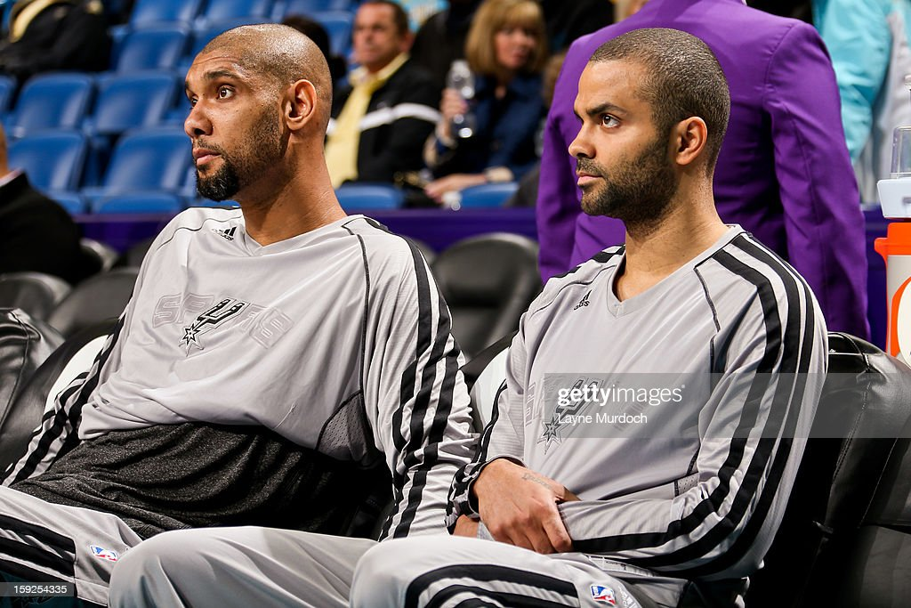Tony Parker #9 and Tim Duncan #21 of the San Antonio Spurs sit on the bench before playing against the New Orleans Hornets on January 7, 2013 at the New Orleans Arena in New Orleans, Louisiana.
