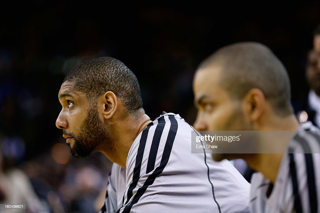Tony Parker #9 and Tim Duncan #21 of the San Antonio Spurs sits on the bench before their game against the Golden State Warriors at Oracle Arena on February 22, 2013 in Oakland, California. The Warriors are wearing new short-sleeved uniforms for the first time. The Warriors won the game in overtime.