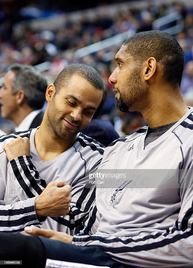 Tony Parker #9 (L) jokes with teammate <a gi-track='captionPersonalityLinkClicked' href=/galleries/search?phrase=Tim+Duncan&family=editorial&specificpeople=201467 ng-click='$event.stopPropagation()'>Tim Duncan</a> #21 of the San Antonio Spurs on the bench during the second half of the Spurs 118-92 win over the Washington Wizards at Verizon Center on November 26, 2012 in Washington, DC.