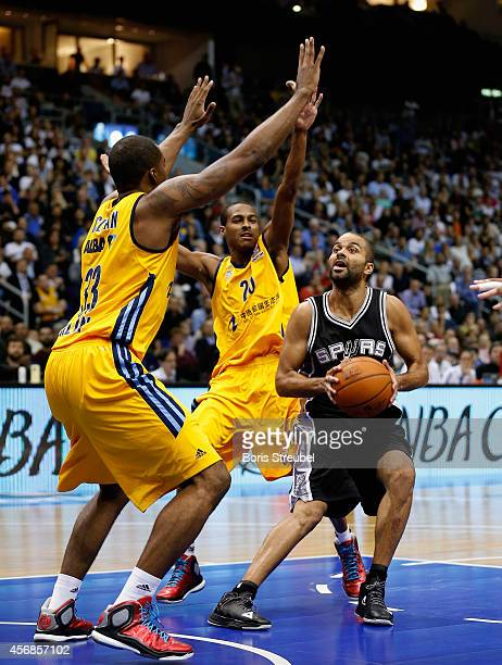 Tony Parker of San Antonio is challenged by Alex Renfroe and Jamel McLean of Berlin during the NBA Global Games Tour 2014 match between Alba Berlin...