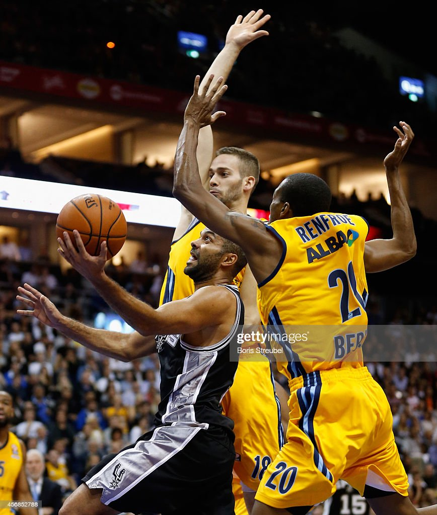Tony Parker (C) of San Antonio is challenged by Alex Renfroe (R) and Jonas Wohlfarth-Bottermann (L) of Berlin during the NBA Global Games Tour 2014 match between Alba Berlin and San Antonio Spurs at O2 World on October 8, 2014 in Berlin, Germany.