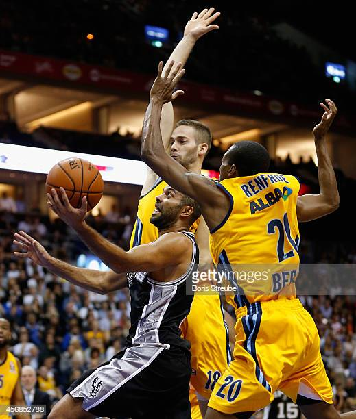 Tony Parker of San Antonio is challenged by Alex Renfroe and Jonas WohlfarthBottermann of Berlin during the NBA Global Games Tour 2014 match between...