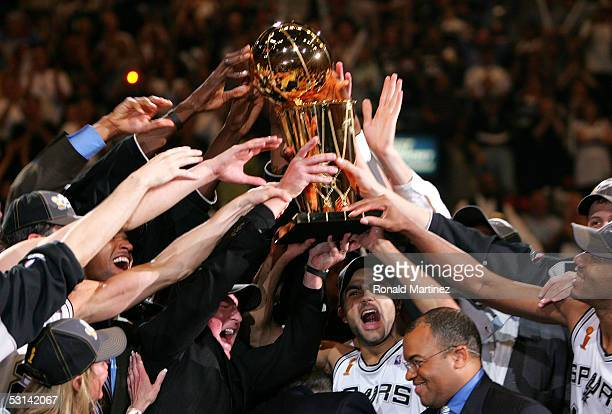Tony Parker of the San Antonio Spurs and his teammates hold up the Larry O'Brien trophy after the Spurs defeated the Detroit Pistons in Game seven of...