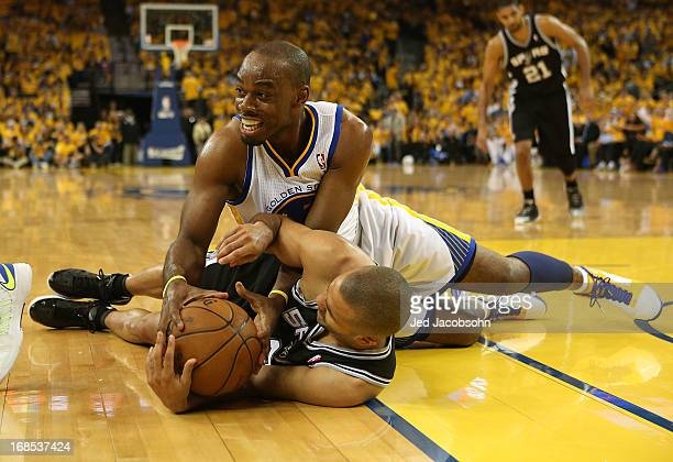 Tony Parker of the San Antonio Spurs battles for the ball with Carl Landry of the Golden State Warriors in Game Three of the Western Conference...