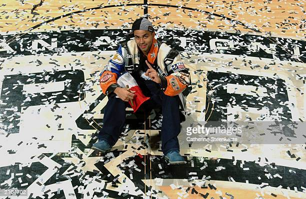 Tony Parker of the San Antonio Spurs celebrates the victory over the New Jersey Nets as he sits in street clothes at center court amidst the confetti...