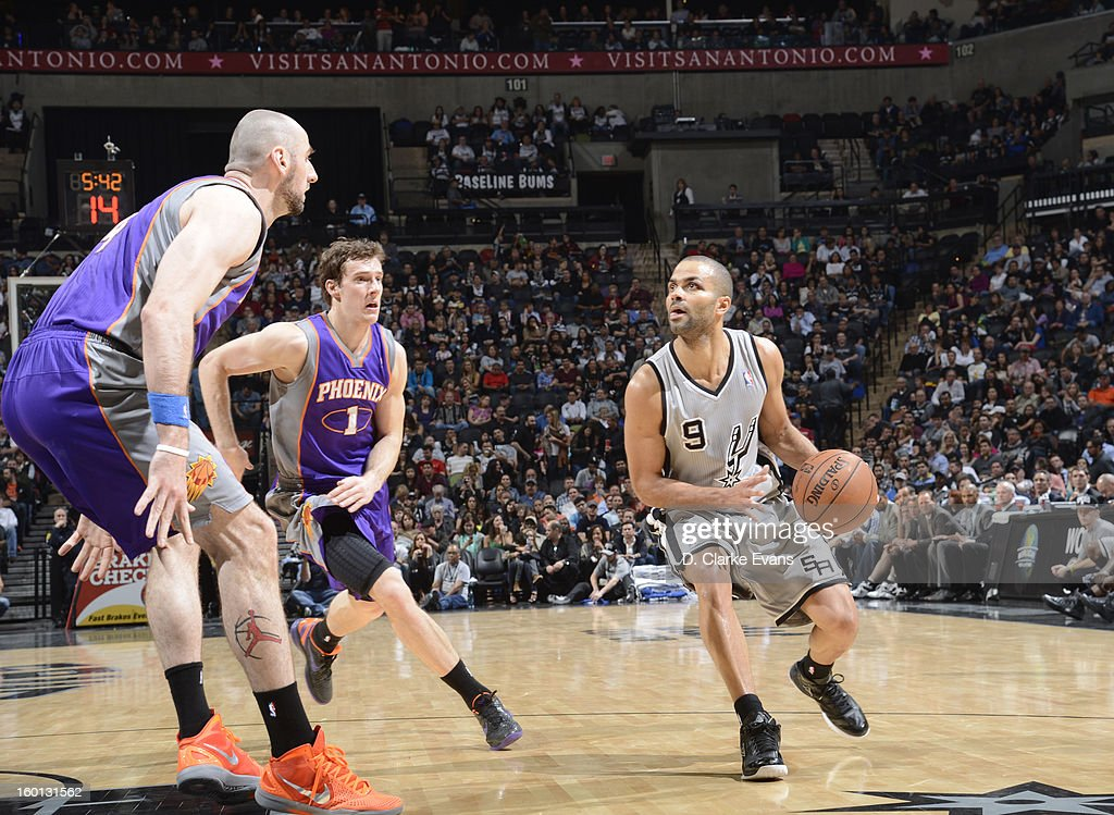 Tony Parker #9 of the San Antonio Spurs controls the ball against Goran Dragic #1 and Marcin Gortat #4 of the Phoenix Suns on January 26, 2013 at the AT&T Center in San Antonio, Texas.