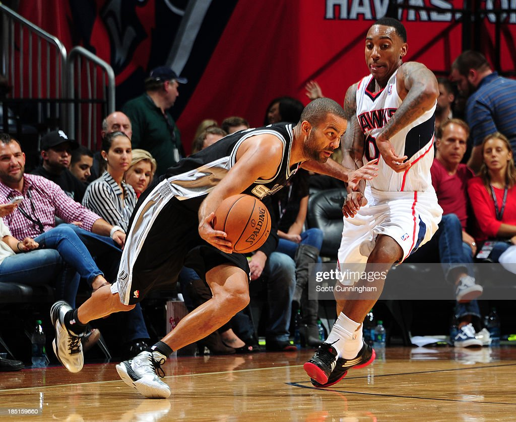 Tony Parker #9 of the San Antonio Spurs drives against <a gi-track='captionPersonalityLinkClicked' href=/galleries/search?phrase=Jeff+Teague&family=editorial&specificpeople=4680498 ng-click='$event.stopPropagation()'>Jeff Teague</a> #0 of the Atlanta Hawks on October 17, 2013 at Philips Arena in Atlanta, Georgia.