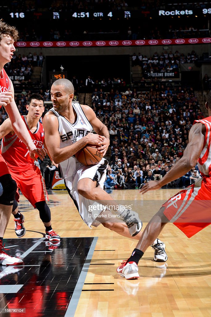Tony Parker #9 of the San Antonio Spurs drives against Omer Asik #3 and Jeremy Lin #7 of the Houston Rockets on December 28, 2012 at the AT&T Center in San Antonio, Texas.