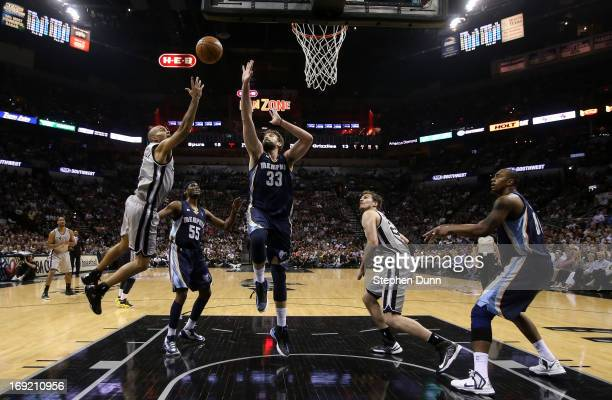 Tony Parker of the San Antonio Spurs drives for a shot attempt in the first half against Keyon Dooling and Marc Gasol of the Memphis Grizzlies during...