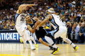 Tony Parker of the San Antonio Spurs drives on Marc Gasol and Jerryd Bayless of the Memphis Grizzlies in the first half during Game Four of the...
