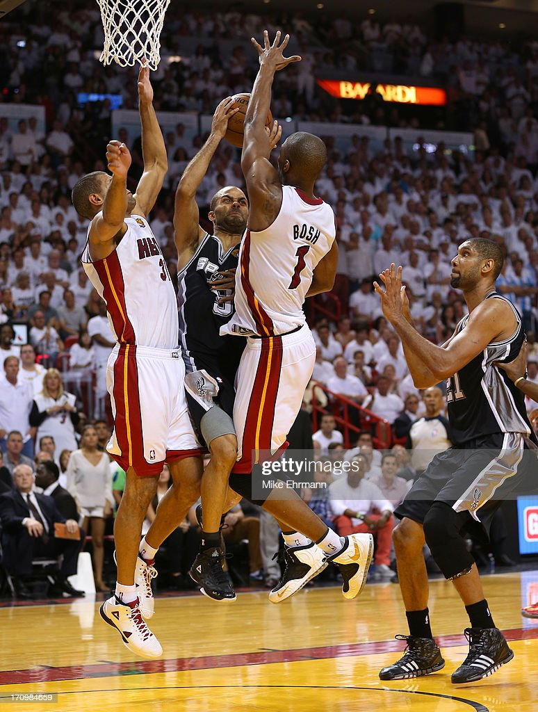 Tony Parker #9 of the San Antonio Spurs drives on Shane Battier #31 and Chris Bosh #1 of the Miami Heat in the fourth quarter during Game Seven of the 2013 NBA Finals at AmericanAirlines Arena on June 20, 2013 in Miami, Florida.