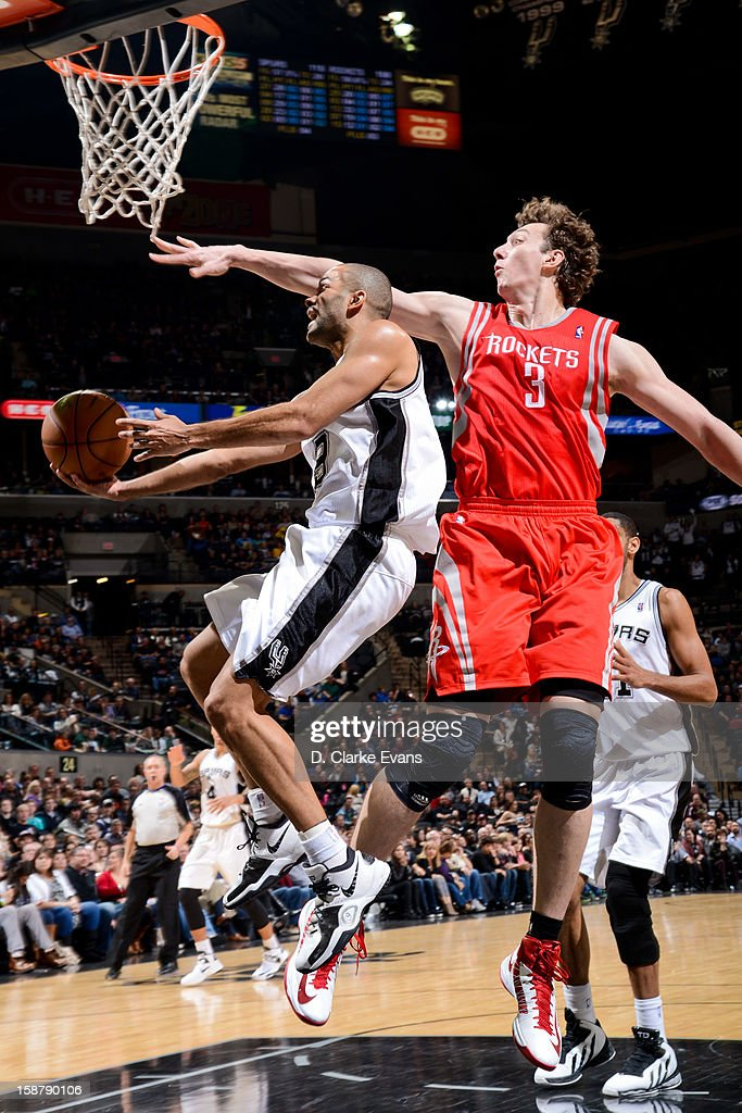 Tony Parker #9 of the San Antonio Spurs drives to the basket against Omer Asik #3 of the Houston Rockets on December 28, 2012 at the AT&T Center in San Antonio, Texas.