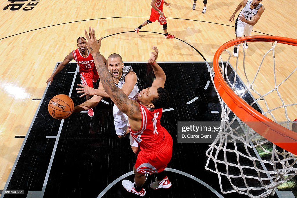 Tony Parker #9 of the San Antonio Spurs drives to the basket against Greg Smith #4 of the Houston Rockets on December 28, 2012 at the AT&T Center in San Antonio, Texas.