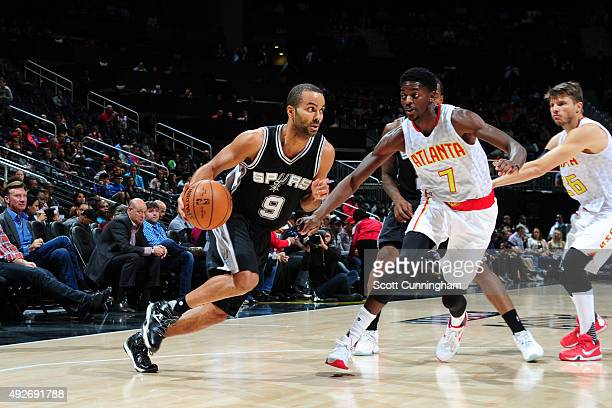 Tony Parker of the San Antonio Spurs drives to the basket against Justin Holiday of the Atlanta Hawks on October 14 2015 at Philips Arena in Atlanta...