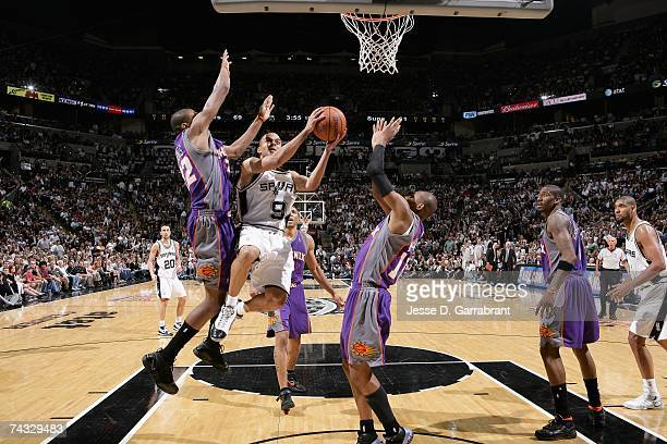 Tony Parker of the San Antonio Spurs goes to the basket against James Jones and Leandro Barbosa of the Phoenix Suns in Game Six of the Western...