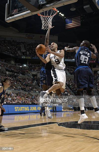 Tony Parker of the San Antonio Spurs goes to the basket between Michael Finley and Walt Williams of the Dallas Mavericks in Game five of the Western...