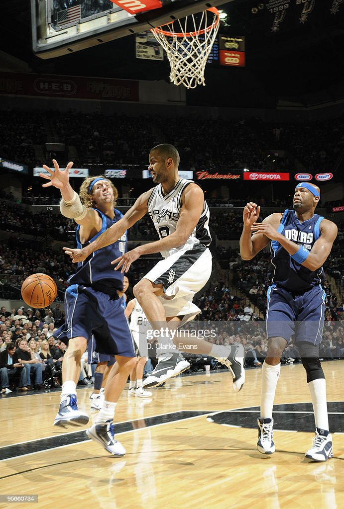 Tony Parker #9 of the San Antonio Spurs jumps to pass against Erick Dampier #25 and Dirk Nowitzki #41 of the Dallas Mavericks on January 8, 2010 at the AT&T Center in San Antonio, Texas.